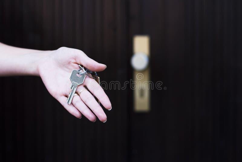 Main femelle tenant des clés de maison images stock