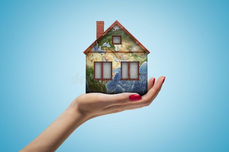 Main femelle tenant la petite maison avec la texture de globe de la terre sur le fond bleu image stock