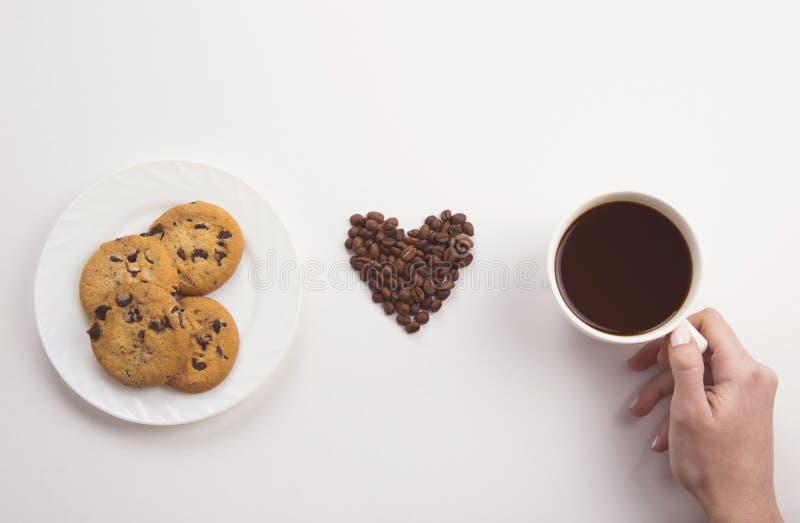 Main femelle tenant la tasse de café, de biscuits de chocolat et de coeur des haricots rôtis sur le fond blanc image stock