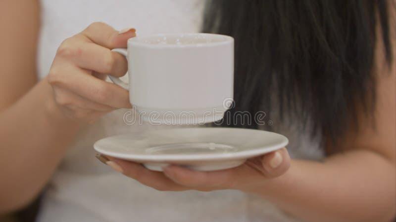Main femelle tenant la tasse de café noir photos libres de droits