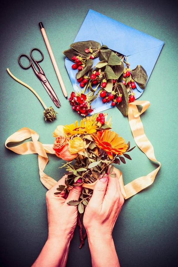 Main femelle tenant le groupe de fleurs d'automne et prenant des dispositions de fleurs de chute sur l'espace de travail de table images stock