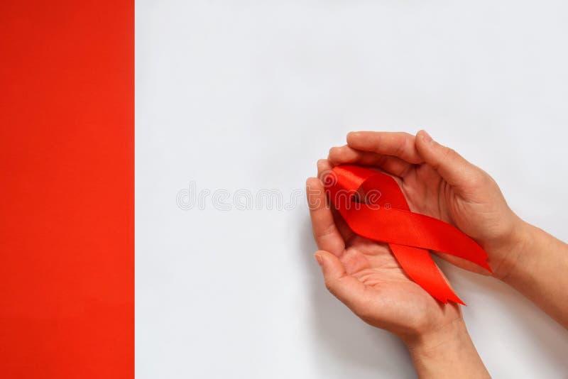 Main femelle tenant le ruban rouge sur le fond blanc Concept de Journée mondiale contre le SIDA photos libres de droits
