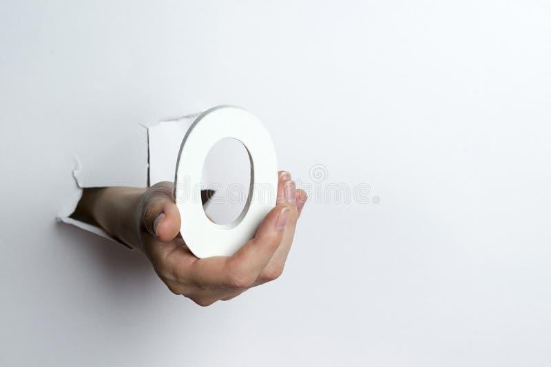 Main femelle tenant un numéro zéro un fond blanc photos stock