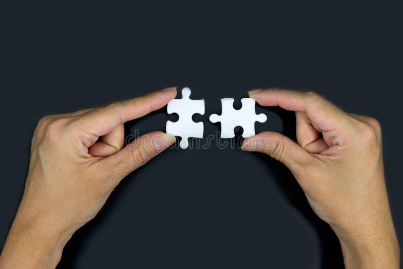 Main femelle tenant un puzzle blanc sur un fond noir photographie stock