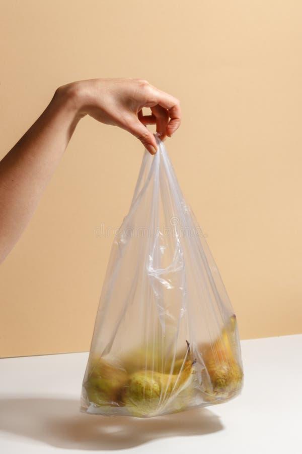 Main femelle tenant un sachet en plastique avec des poires photo libre de droits