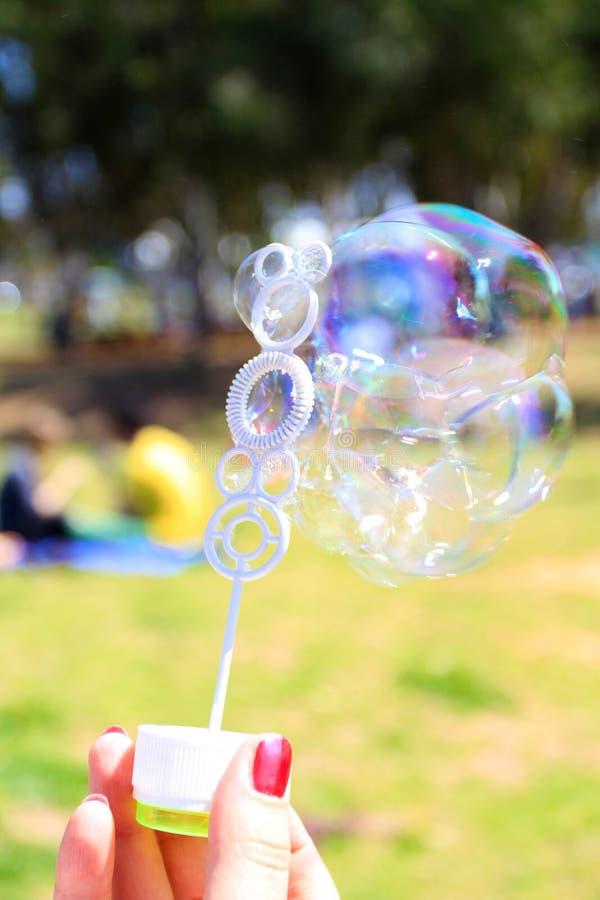 Main femelle tenant une baguette magique pour déclencher des bulles de savon sur le vert images libres de droits
