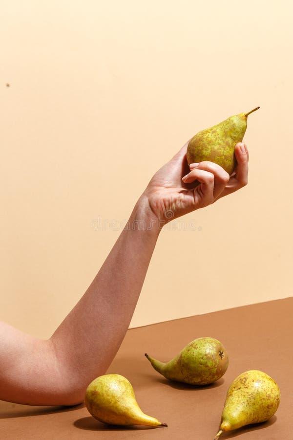 Main femelle tenant une poire verte photographie stock libre de droits