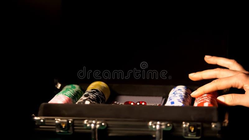 Main femelle touchant la puce de jeu, pariant dans le tisonnier, dépendance de jeu, chance image stock
