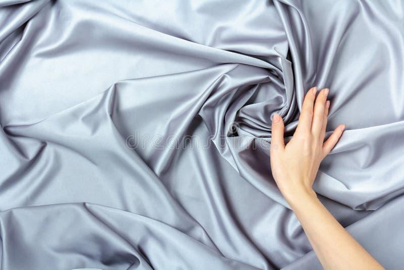 Main femelle touchant la texture de luxe élégante douce de tissu de soie ou de satin photo libre de droits