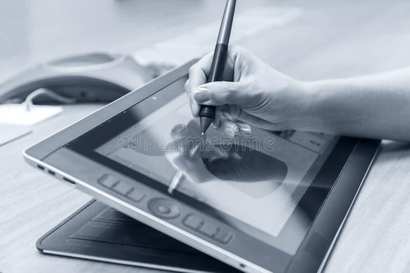 Main femelle utilisant le comprimé graphique numérique et le stylet tout en travaillant au bureau moderne Plan rapproché photo mo photos stock
