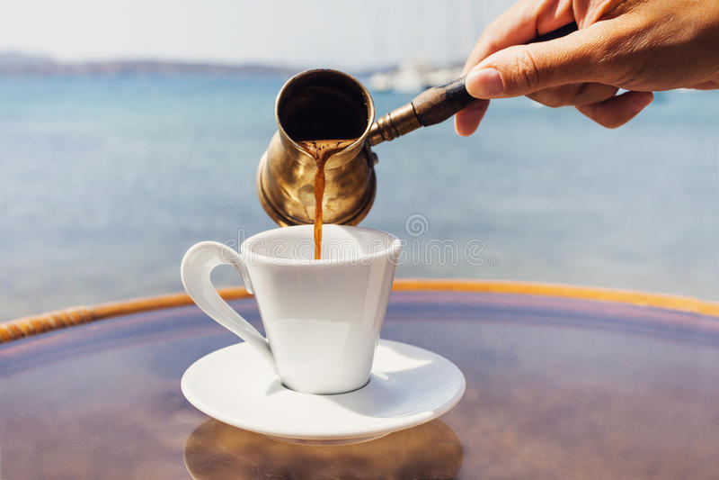 Main femelle versant le café grec traditionnel dans un café avec une mer sur le fond photographie stock libre de droits