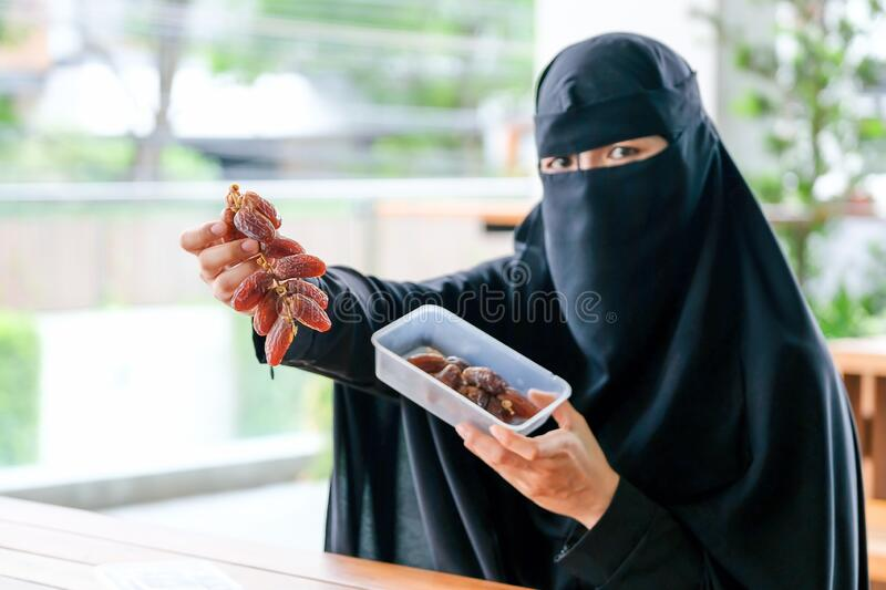 Main focus at date palm on hand of Muslim girl with face cover hijab for the concept of fasting festival during Ramadan.  royalty free stock photo