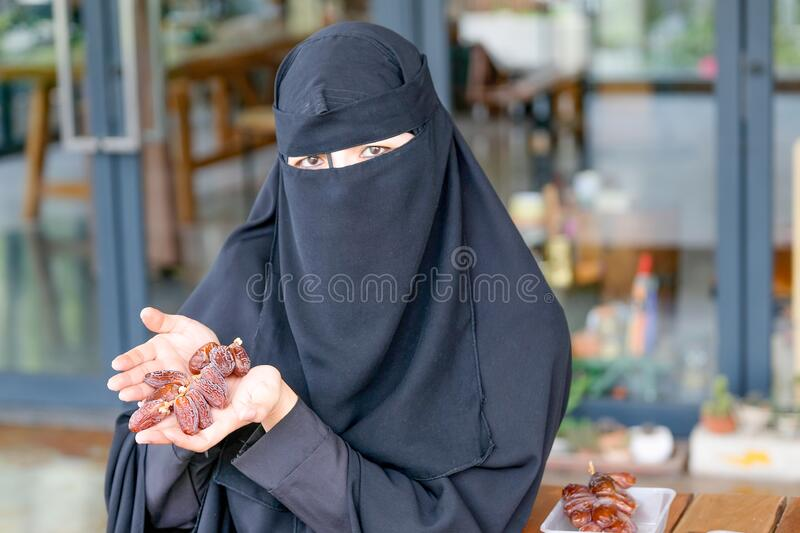 Main focus at date palm on hand of Muslim girl with face cover hijab for the concept of fasting festival during Ramadan.  stock photography