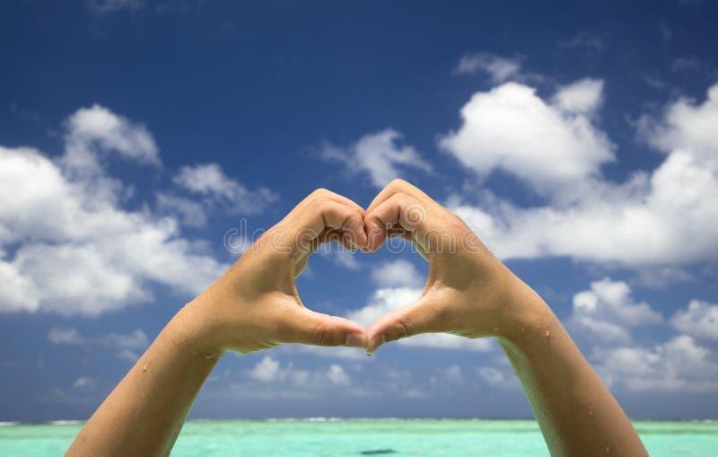 Main formant un coeur sur la plage image stock