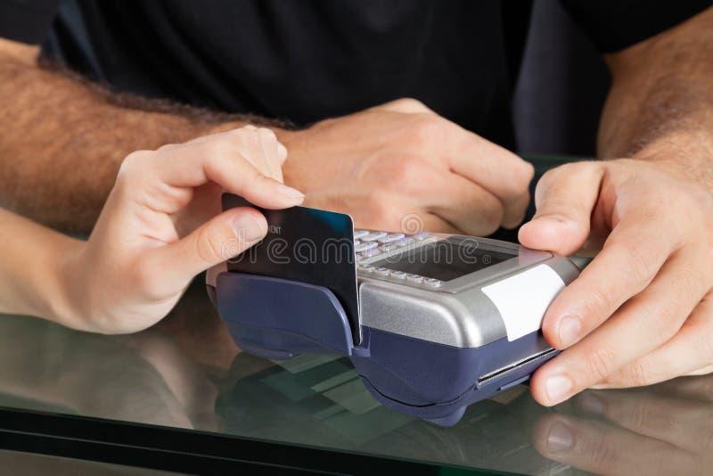 Main frappant à toute volée la carte de crédit par le terminal au salon photographie stock
