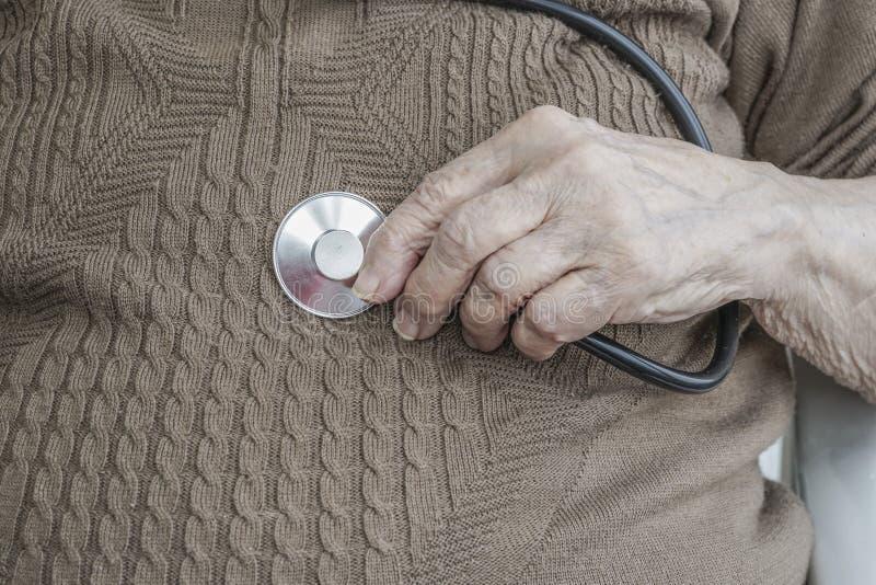 Main froissée tenant le stéthoscope sur écouter son estomac image libre de droits