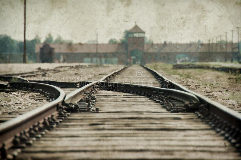 Main gate and railroad to nazi  concentration camp of Auschwitz Birkenau. Effect with grunge background, fake old photo. Main gate and railroad to nazi stock photography