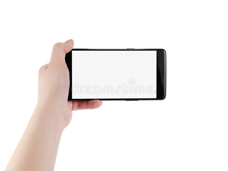 Main gauche de l'adolescence femelle jugeant le smartphone d'isolement sur le blanc photographie stock