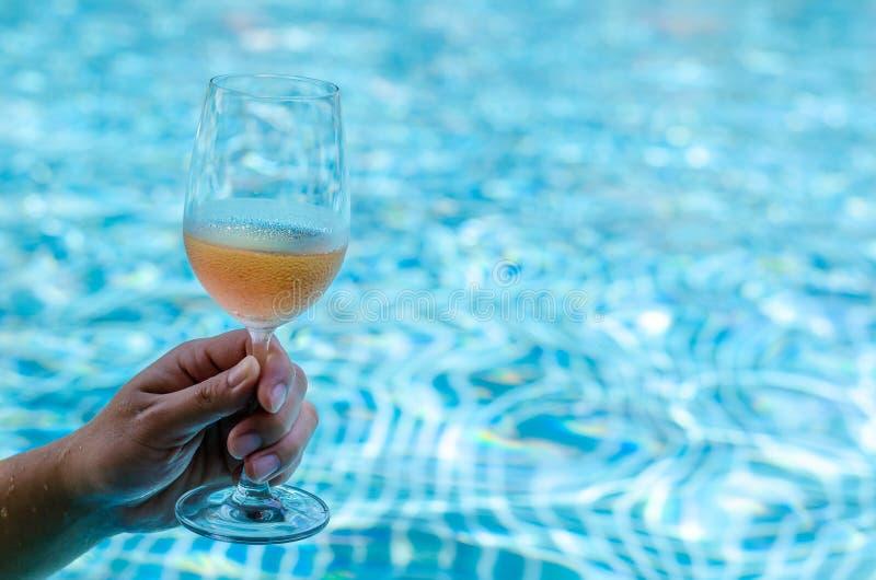 Main grillant avec des verres de vin de Rose à la piscine photographie stock libre de droits