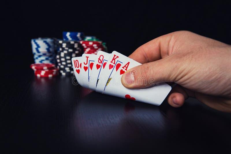 Main haute étroite de la vérification de joueur de poker de jeune homme prudente à ses cartes de jeu photographie stock