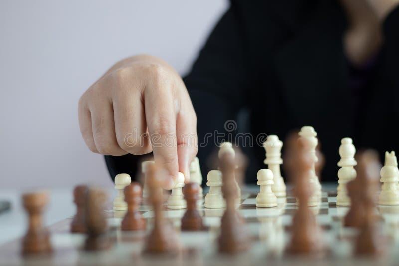 Main haute étroite de tir de femme d'affaires jouant l'échiquier pour gagner en tuant le roi de la concurrence opposée d'affaires photos libres de droits