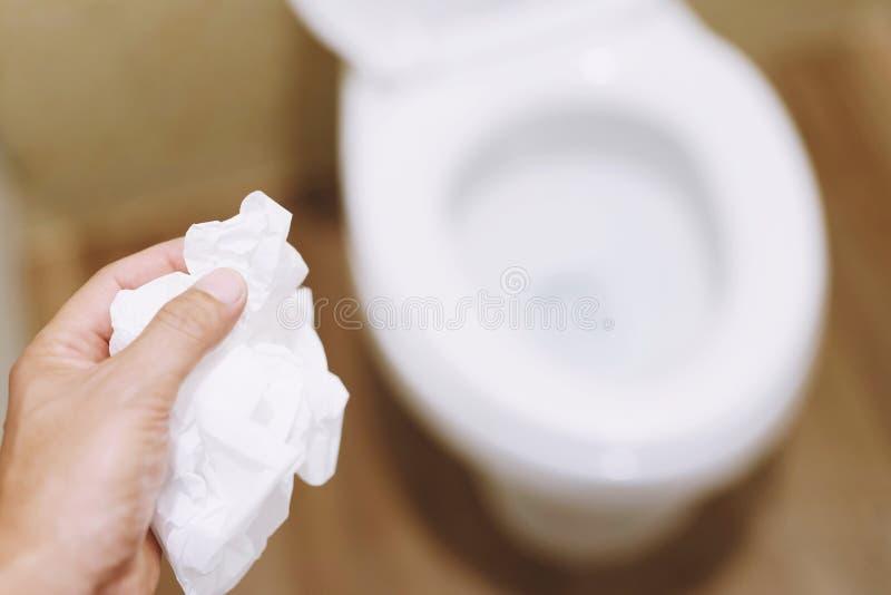 Main haute ?troite tenant un tissu ? jeter dans la cuvette des toilettes images stock