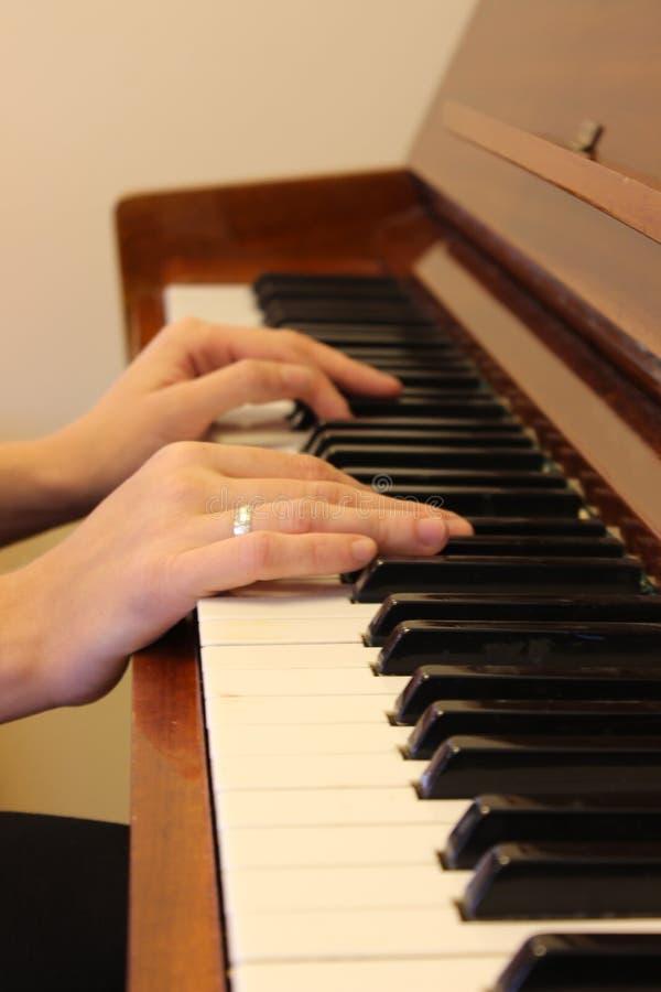 Main heureuse du ` s de femme jouant le piano pendant le matin images stock