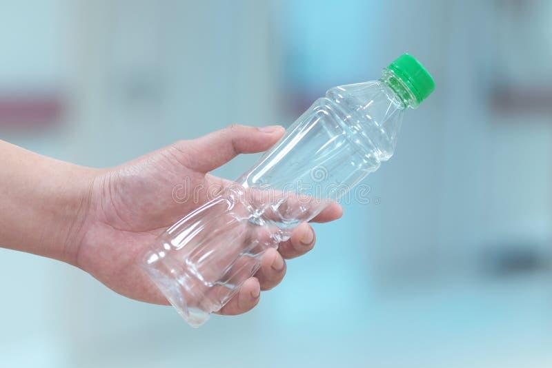 Main humaine et bouteille en plastique images libres de droits