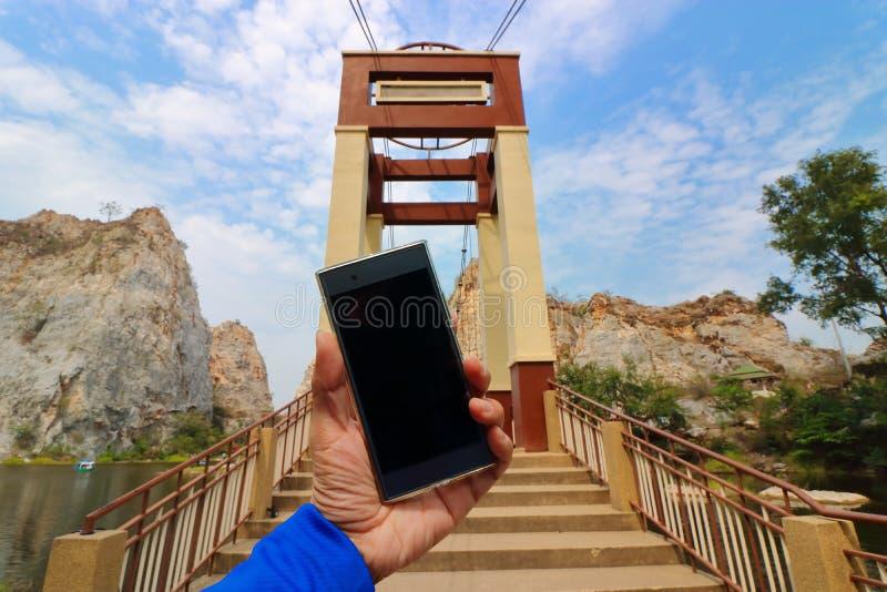 Main humaine tenant le téléphone intelligent mobile avec le fond de pont et de montagne et de lac de pierre images libres de droits