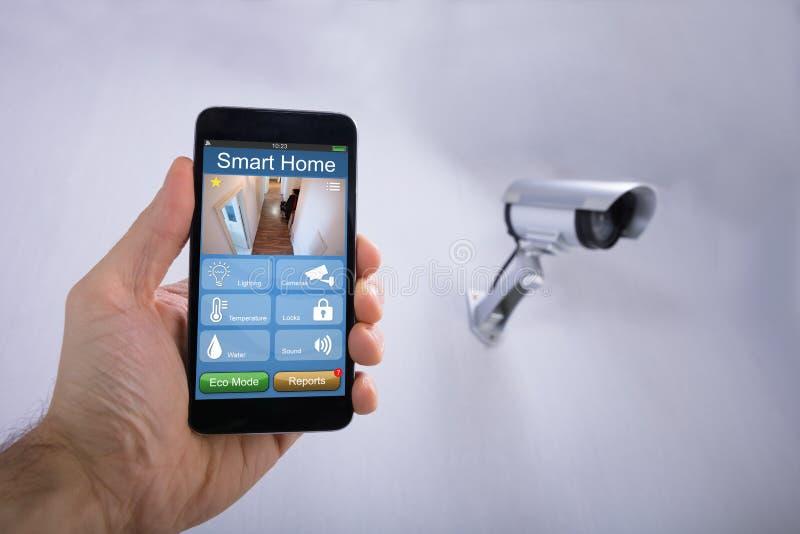 Main humaine utilisant l'application à la maison futée sur Smartphone photographie stock libre de droits