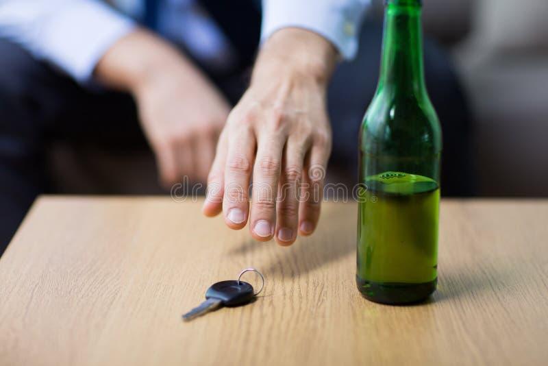 Main ivre de conducteur prenant la clé de voiture de la table photographie stock