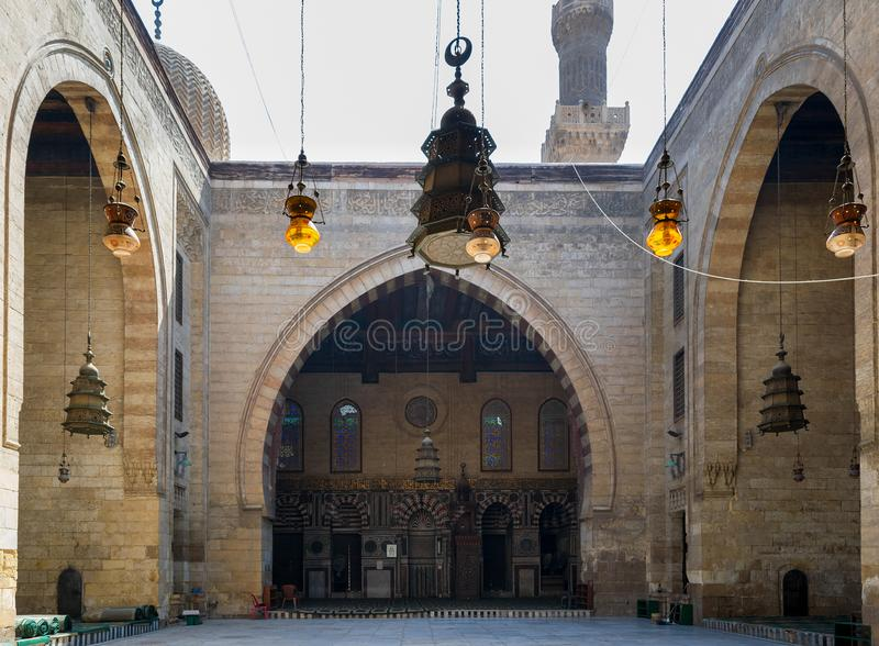 Main iwan - arch - at the courtyard of historic Mamluk era mosque of Al Ashraf Barsbay, Cairo, Egypt. Main iwan - arch - and minaret at the courtyard of public royalty free stock photo