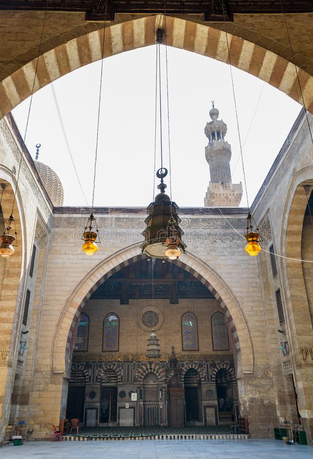 Main iwan - arch - at the courtyard of historic Mamluk era mosque of Al Ashraf Barsbay, Cairo, Egypt. Main iwan - arch - and minaret at the courtyard of public royalty free stock photos