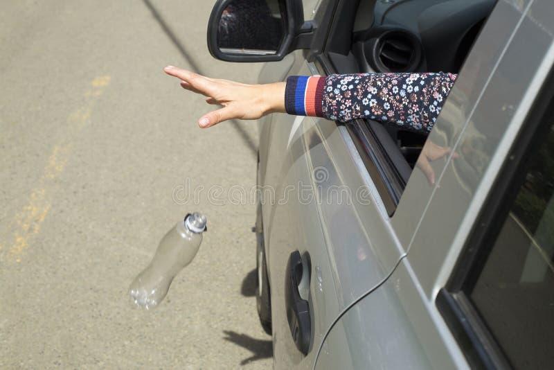 Main jetant la bouteille en plastique sur la route images libres de droits