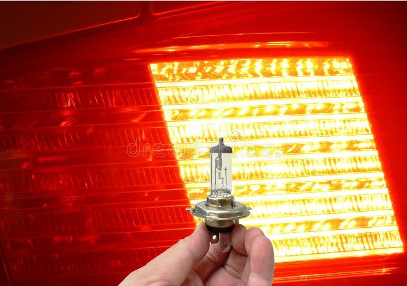 Main jugeant des pièces de rechange de véhicule d'ampoule d'halogène sur la lampe arrière de voiture brillantes à l'arrière-plan  image stock