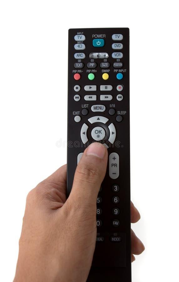 Main jugeant une TV à télécommande images stock