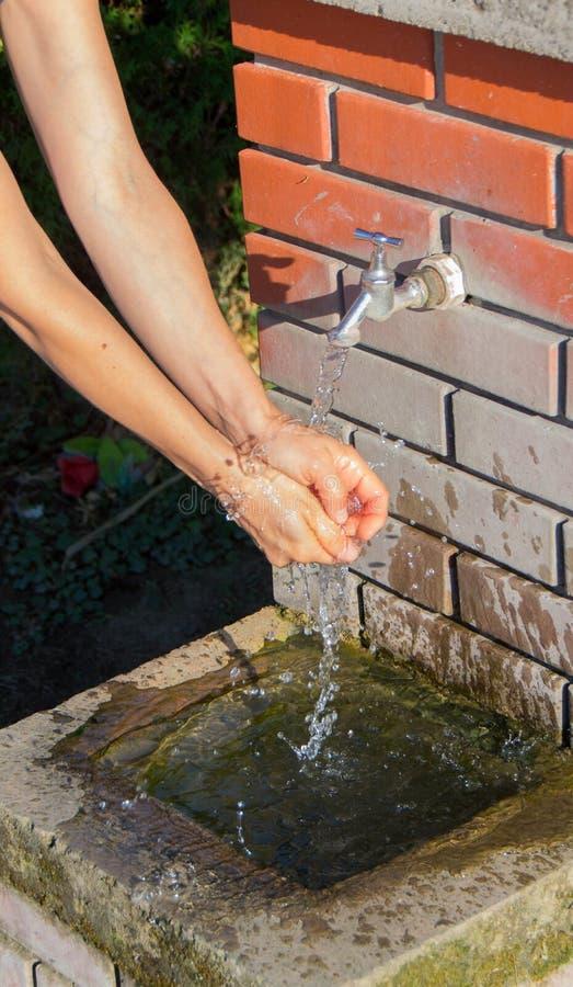 Main lavant à une fontaine publique photos stock