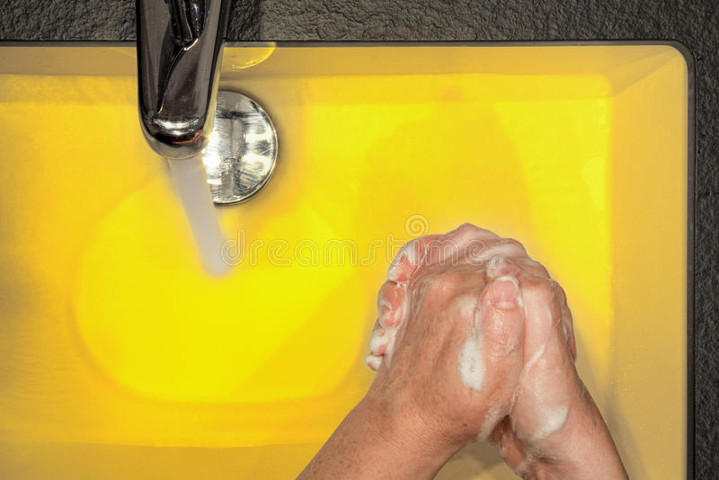 Main lavant en jaune photo stock
