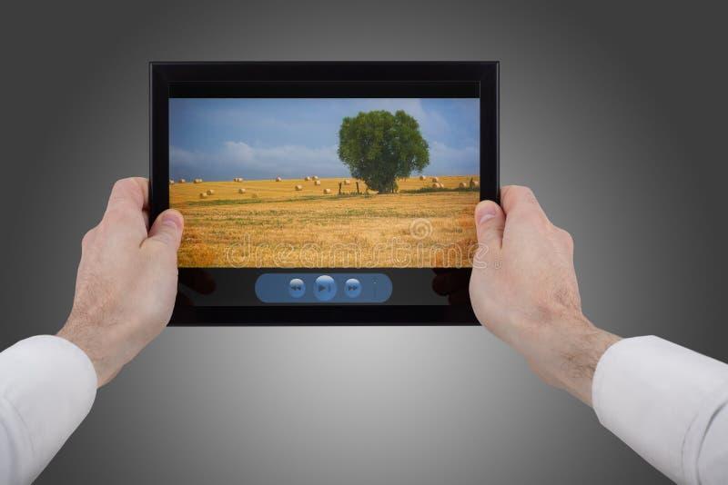 Main mâle retenant un PC de touchpad affichant un film photographie stock