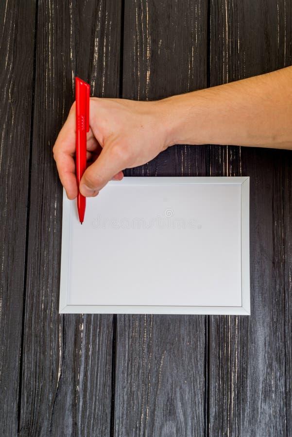 Main masculine écrite sur le cadre photo stock