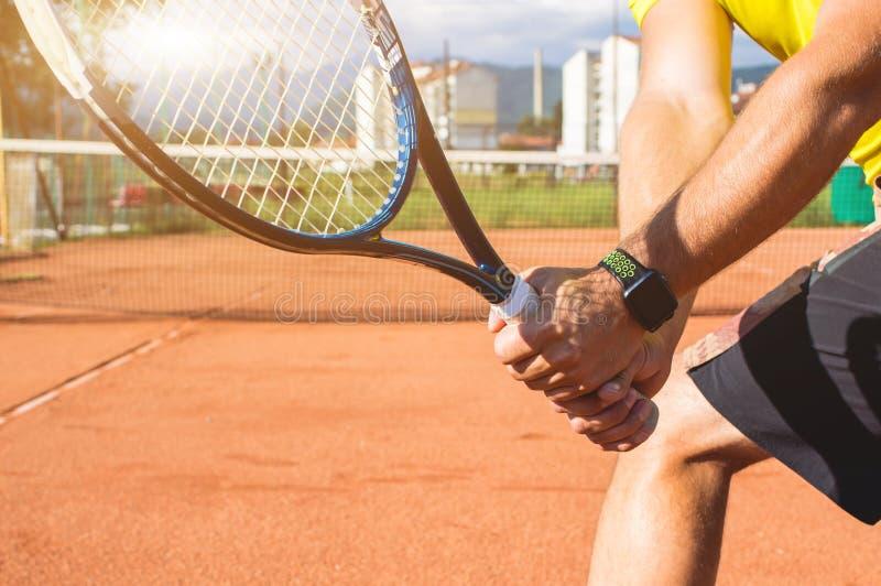Main masculine avec la raquette de tennis image libre de droits