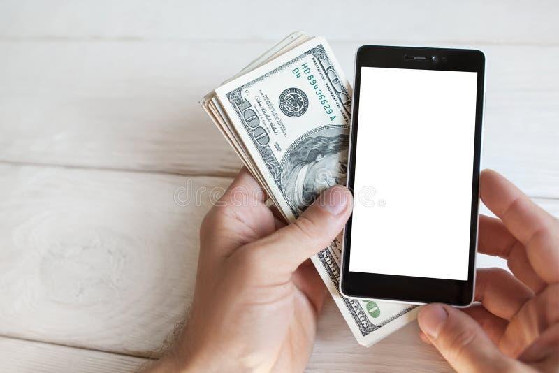 Main masculine avec le smartphone et l'argent liquide américain, mokup photographie stock libre de droits
