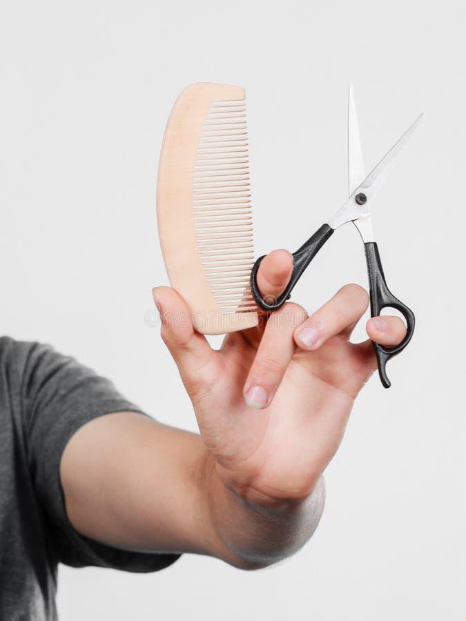 Main masculine avec les ciseaux et le peigne image stock