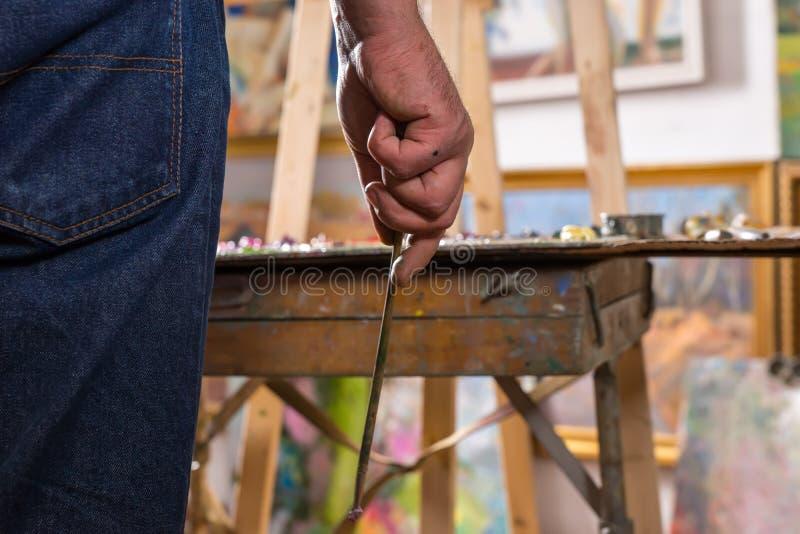 Main masculine d'artiste tenant un pinceau minuscule photos libres de droits