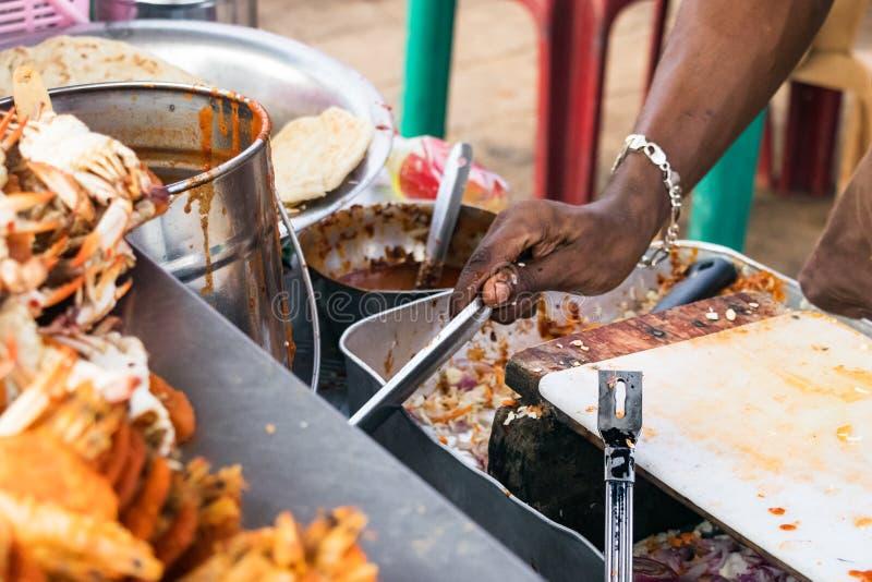 Main masculine d'un cuisinier faisant cuire des fruits de mer dehors sur un marché en plein air à Colombo, Sri Lanka photo libre de droits