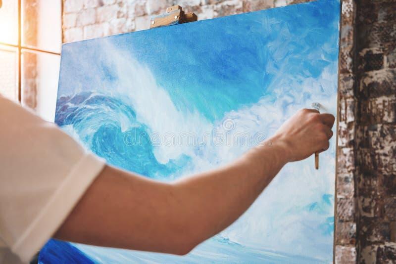 Main masculine de plan rapproché d'artiste tenant le pinceau sur le fond de la toile sur le chevalet Ressac professionnel de dess image stock