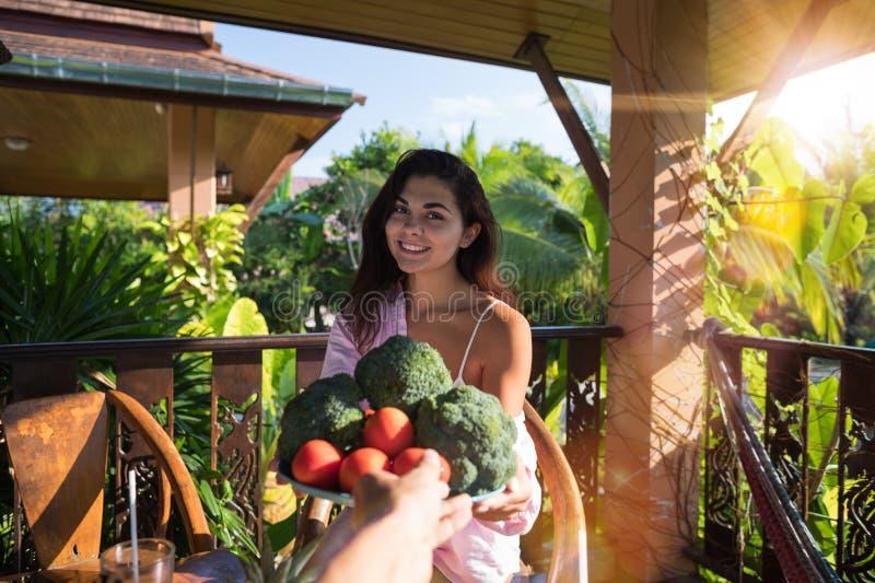 Main masculine donnant le beau plat de femme de la fille Sit On Summer Terrace In de sourire heureux des légumes frais POV tropic photographie stock