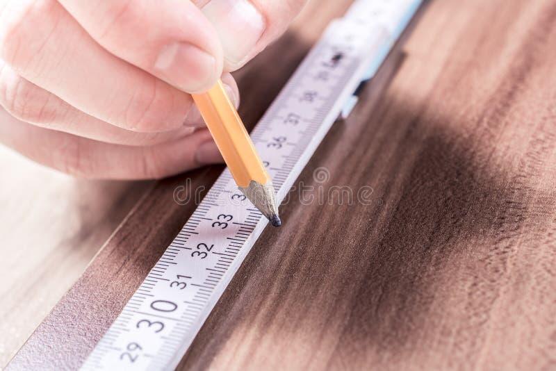 Main masculine faisant Mark At The Measuring Point du critère se pliant d'A sur un conseil en bois image libre de droits