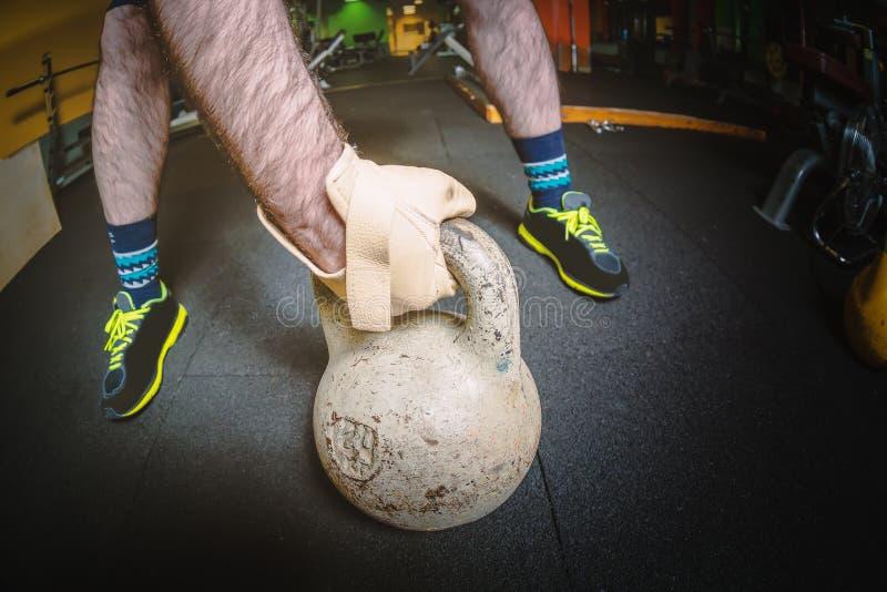 Main masculine forte avec le kettlebell gris au centre de sports de forme physique de gymnase Concept de sports photo stock