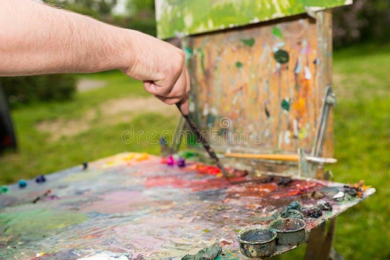 Main masculine mélangeant des couleurs foncées à un pinceau photo stock